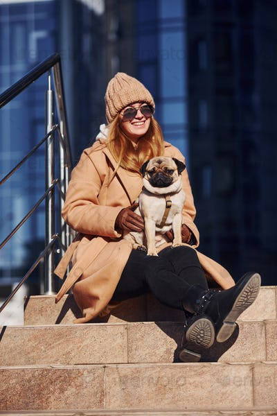 Woman in warm clothes have a walk with her little pug dog near business building that on background
