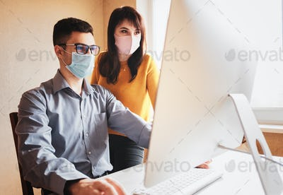 Colleagues in masks near the computer