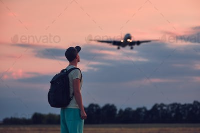 Man looking up at flying airplane