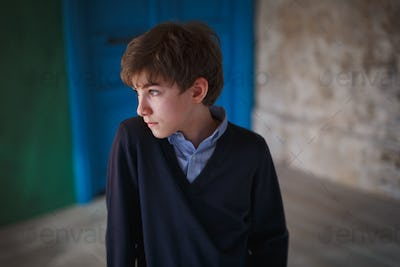 Serious pensive cute teen boy standing in loft style room and looking away.