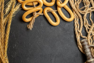 Ring-shaped cookies spike rope and ancient pottery on dark background