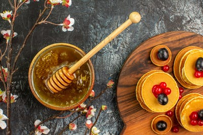 Above view of ring-shaped cookies fruit pancakes honey in a bowl and black cherries on gray table