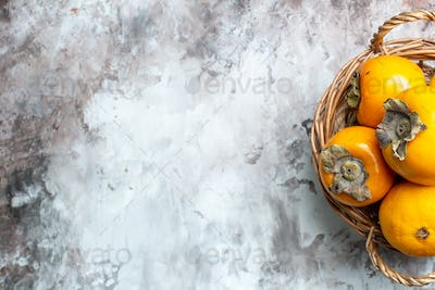 top view fresh persimmons inside basket on light background color mellow healthy life free space