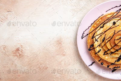 Half shot of Classic American homemade pancakes decorated with chocolate syrup on a white background