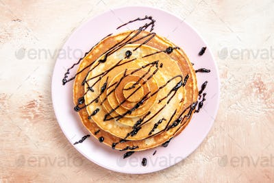 Classic American homemade pancakes decorated with chocolate syrup in a white plate