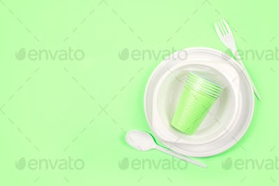 Multicolored bright plastic disposable tableware on green background. Disposable white plastic plate