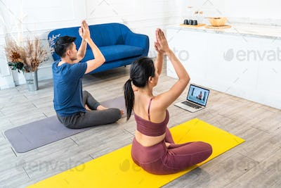 Couple practicing yoga from online video