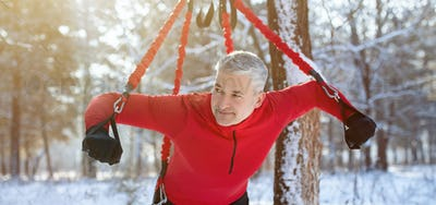 Strong senior man doing bungee fitness exercises, working out outdoors on winter morning, panorama