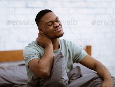 Black Man Massaging Neck Suffering Osteoarthritis Waking Up In Bedroom