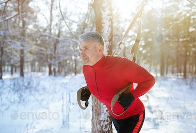 Strong mature man doing TRX fitness workout at snowy winter park. Outdoor endurance exercises