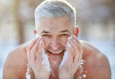 Happy senior man washing his face with snow, developing resistance to cold at frosty winter park