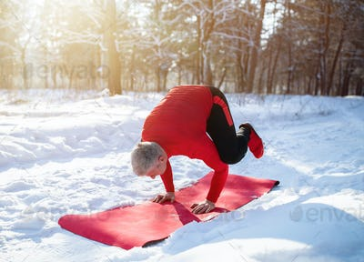 Fit senior man having outdoor yoga practice in winter at snowy forest