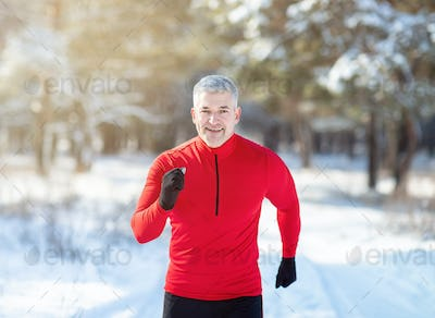 Cross country running in winter. Happy fit senior man jogging in snowy forest on sunny morning