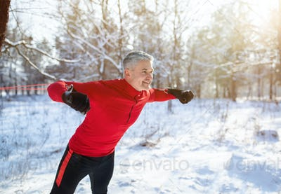 Winter sports concept. Handsome senior man training with fitness straps at snowy forest, copy space