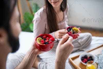 Unrecognizable young couple in love eating breakfast on bed indoors at home.