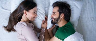 Top view of young couple in love lying on bed indoors at home.