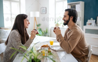Young couple in love eating hamburgers indoors at home.