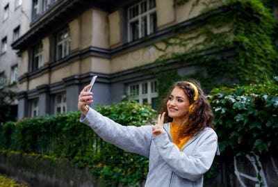 Young woman with smartphone outdoors on street, video for social media concept.