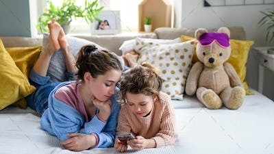 Sisters indoors at home, using smartphone. Lockdown concept.