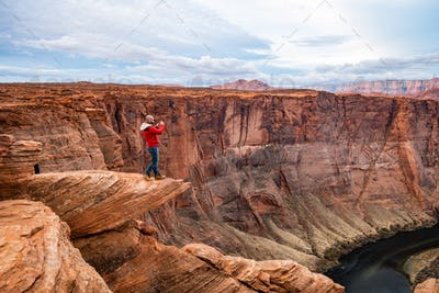 Man standing on a cliff over Colorado river at Horseshoe bend viewpoint at Glen Canyon, Arizona, USA
