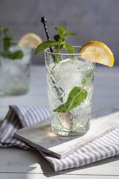Refreshing drink with lemon and mint in a glass on a white wooden board