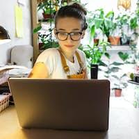 Woman gardener remote working on laptop, communicates on internet in home garden, greenhouse