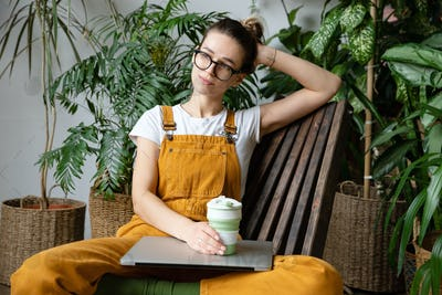 woman gardener resting after work, sitting on wooden chair in home greenhouse, hold reusable tea mug