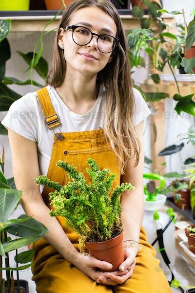 Woman gardener holding fern in plastic pot, sitting in home garden. Love of houseplants, hobby.