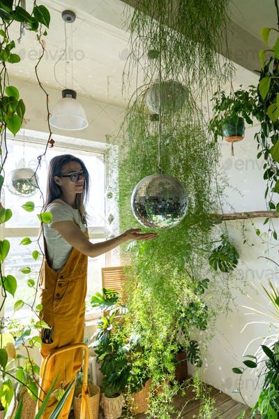 Woman florist touches the hanging disco ball. Greenery at home. Love of plants. Indoor cozy garden.
