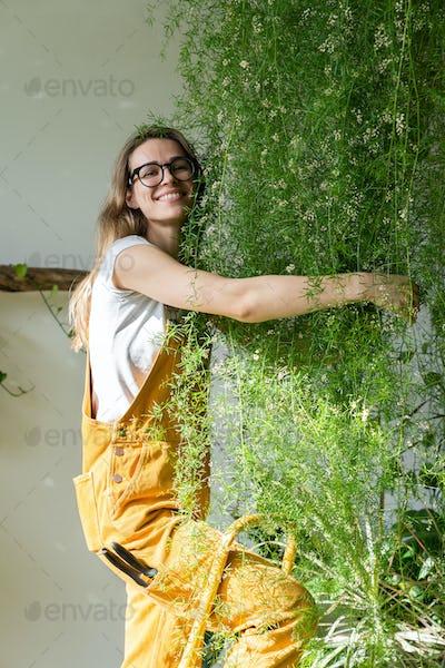 Joyful woman gardener standing on stepladder embracing lush asparagus fern plant in flower store.