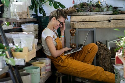 woman gardener sitting on the floor in flower shop working on laptop, smiling talking on video call