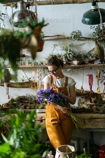 happy florist woman charmed with pleasant gift, smiling, looking at a bouquet of irises flowers