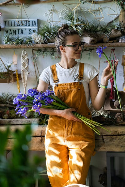 florist woman charmed with pleasant gift smiling looking at bouquet of irises flowers. Indoor garden