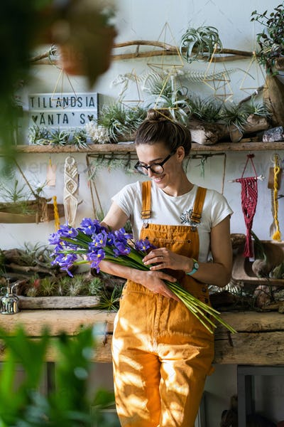 happy florist woman charmed with pleasant gift, smiling, looking at a bouquet of irises flowers.