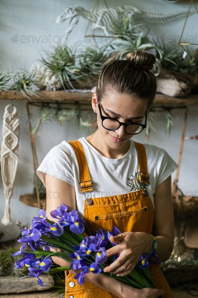 florist woman charmed with pleasant gift, smiling looking at bouquet of irises flowers. home garden
