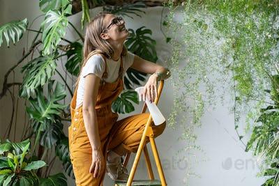 Happy gardener woman holding pulverizer spray, smiling takes a break from work sitting on stepladder