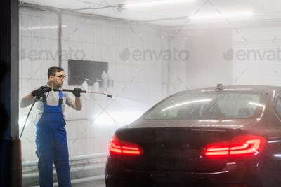 Worker cleaning automobile with high pressure water jet at car wash
