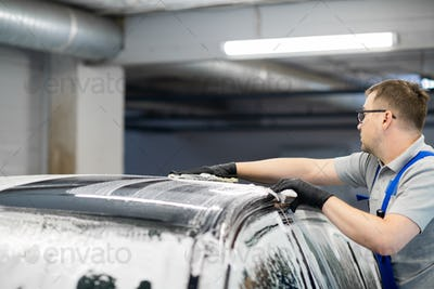 Man washing the car after shampooing the bodywork wiping the car surface with a special cleaning