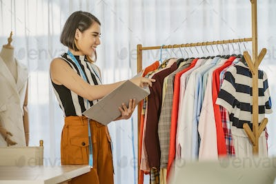 Young Asian designer woman choosing and checking multicolor clothes with checklist