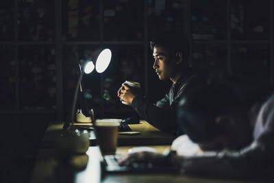 Asian businessman working hard late with his technology laptop in office,