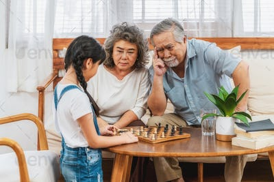 Asian couple Grandparent with grandchild playing the chess with Use thought together,