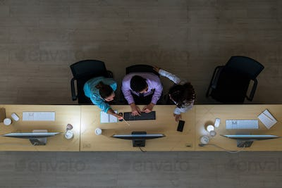 Top view of Three Asian customer care service working hard late in night shift at office