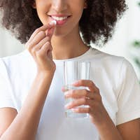 Cheerful young african american woman takes a pill of vitamins and drinks with glass of water