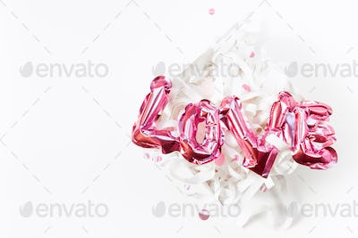 Love concept. Inflatable pink balloon with letters