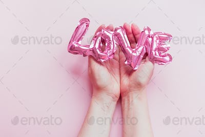 Love concept. Inflatable pink balloon in hands