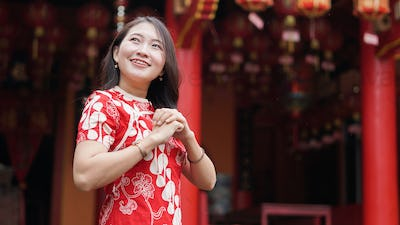 Asian Chinese woman in a cheongsam dress with congratulations gest at vihara