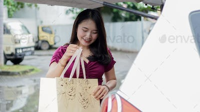 Smiling asian woman putting her shopping bags into the car trunk