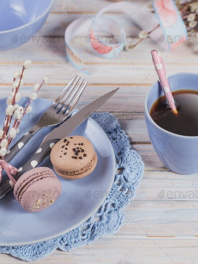 Easter Table Setting with Coffee, Macaroon Cookies, Willow Branches and Cutlery