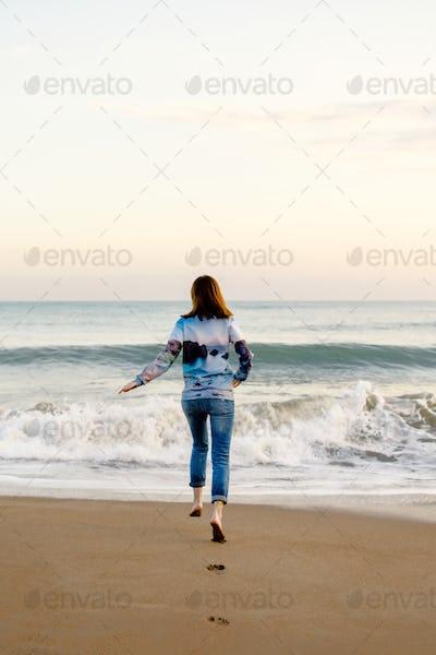 Woman runs into the sea. Storm, sunset.