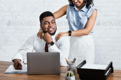Young black woman massaging her male colleague's shoulders, young guy enjoying her sexual